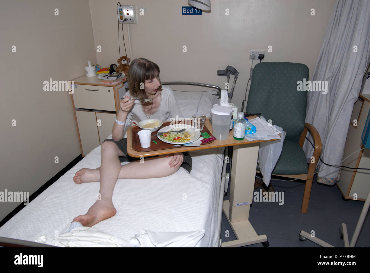 Female patient in cancer ward eating lunch upon arrival and