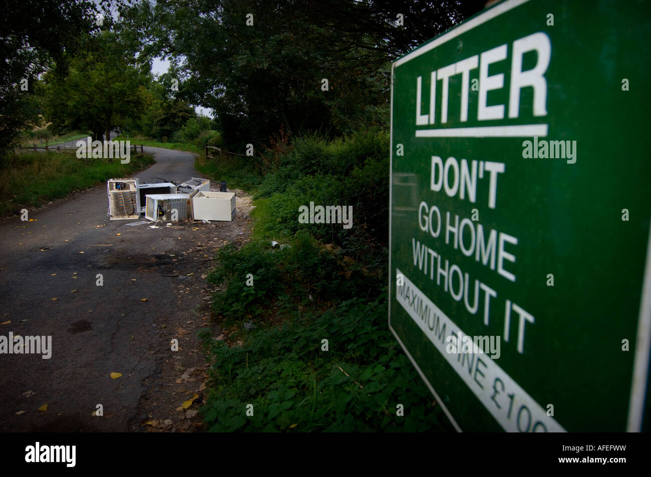 Fly-tipping: a council sign appeals for litter to be taken home with white goods dumped in background. Picture by - Stock Image