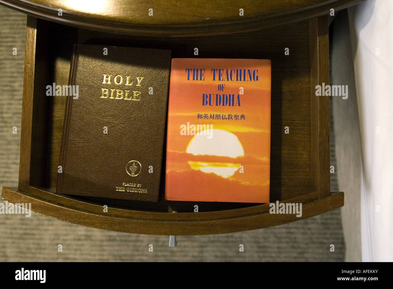 Bible and Teachings of Buddha in asian hotel room - Stock Image
