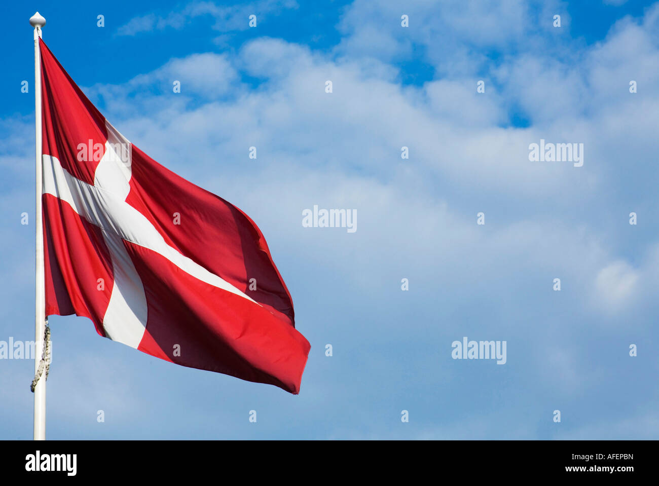 Danish Flag against a blue sky with clouds - Stock Image
