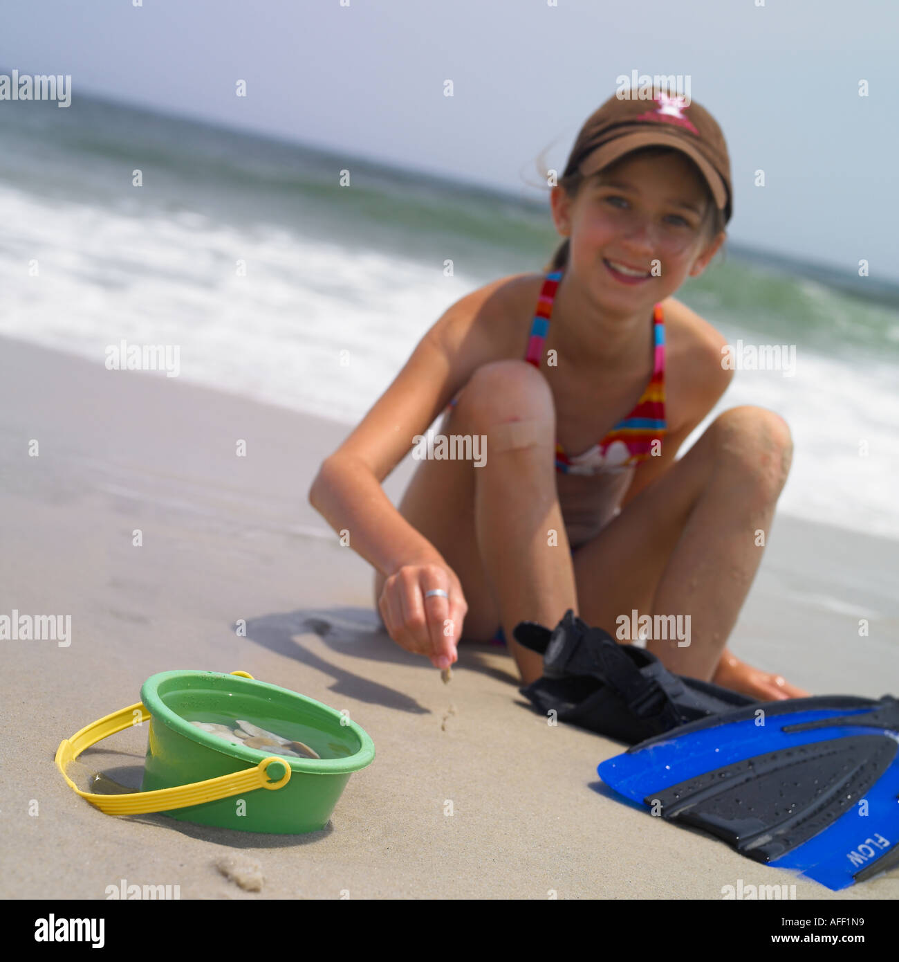 portrait of a young girl with a toy bucket and a pair of fins - Stock Image