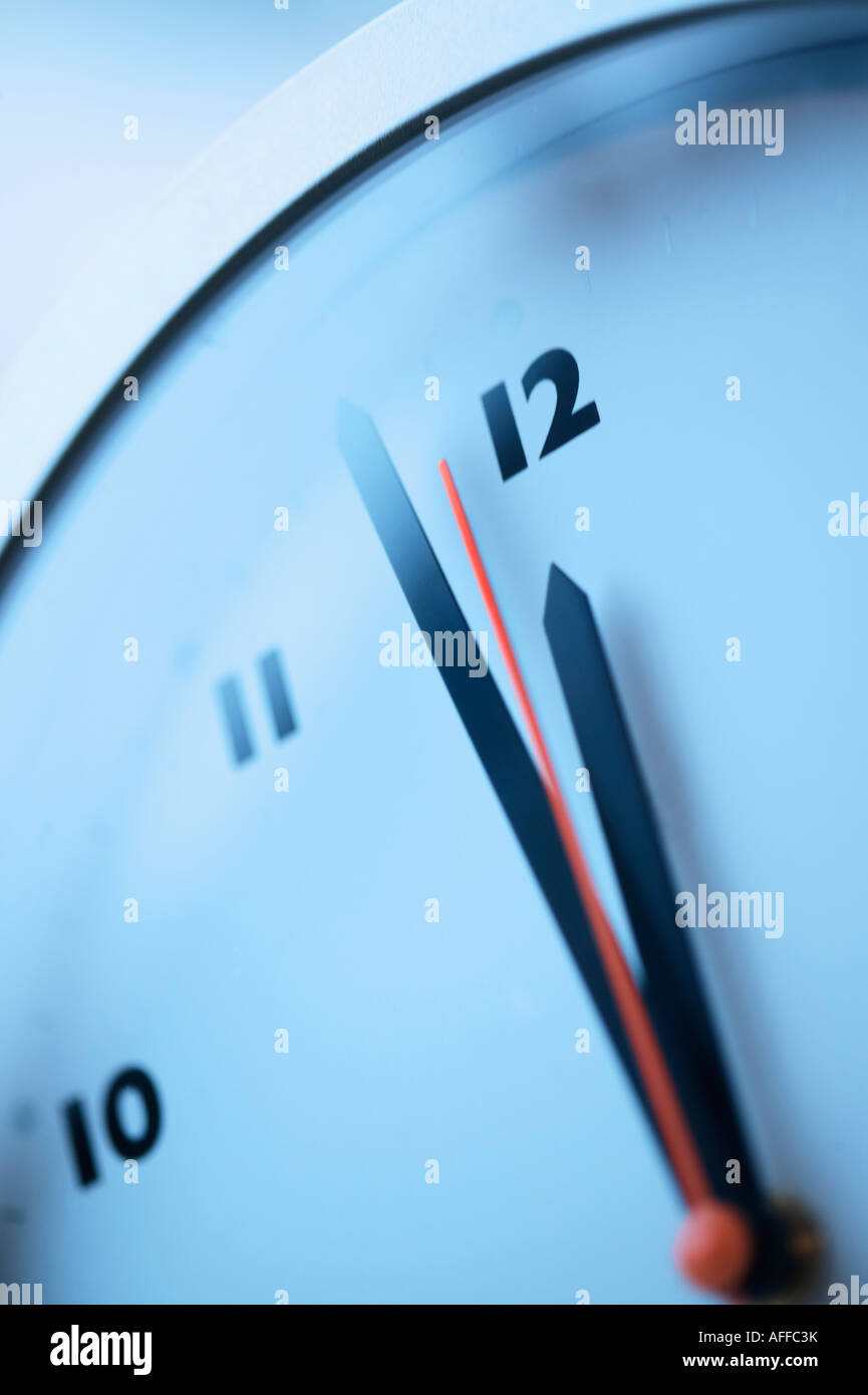 Close up of a red second hand approaching midnight on a wall clock - Stock Image