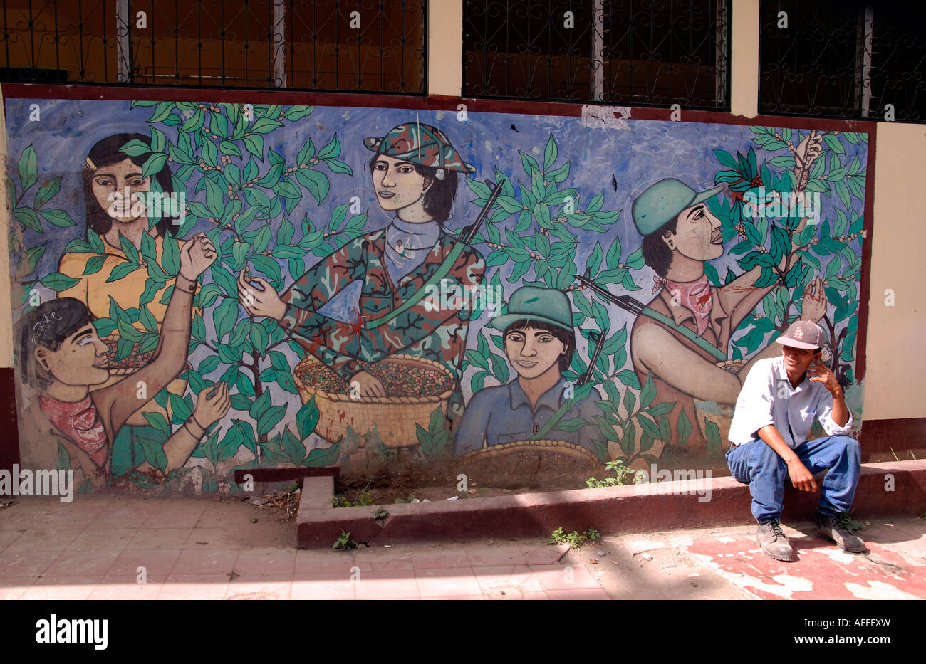 Man sitting in front of revolutionary wall mural, Jinotega, Nicaragua Stock Photo