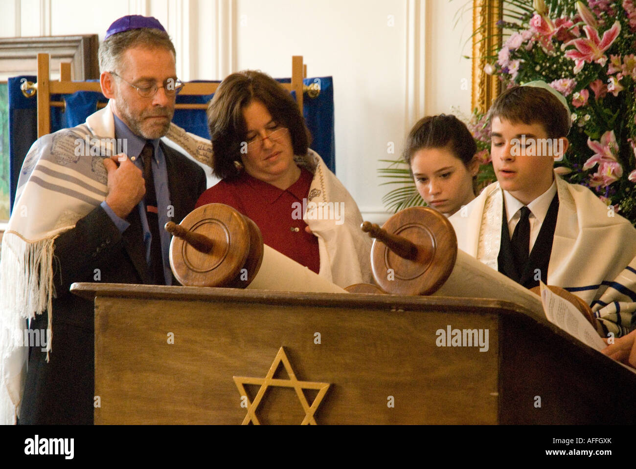 Bar Mitzvah boy (twin) reads from the torah alongside his parents and sister ( Bat mitzvah girl) - Stock Image