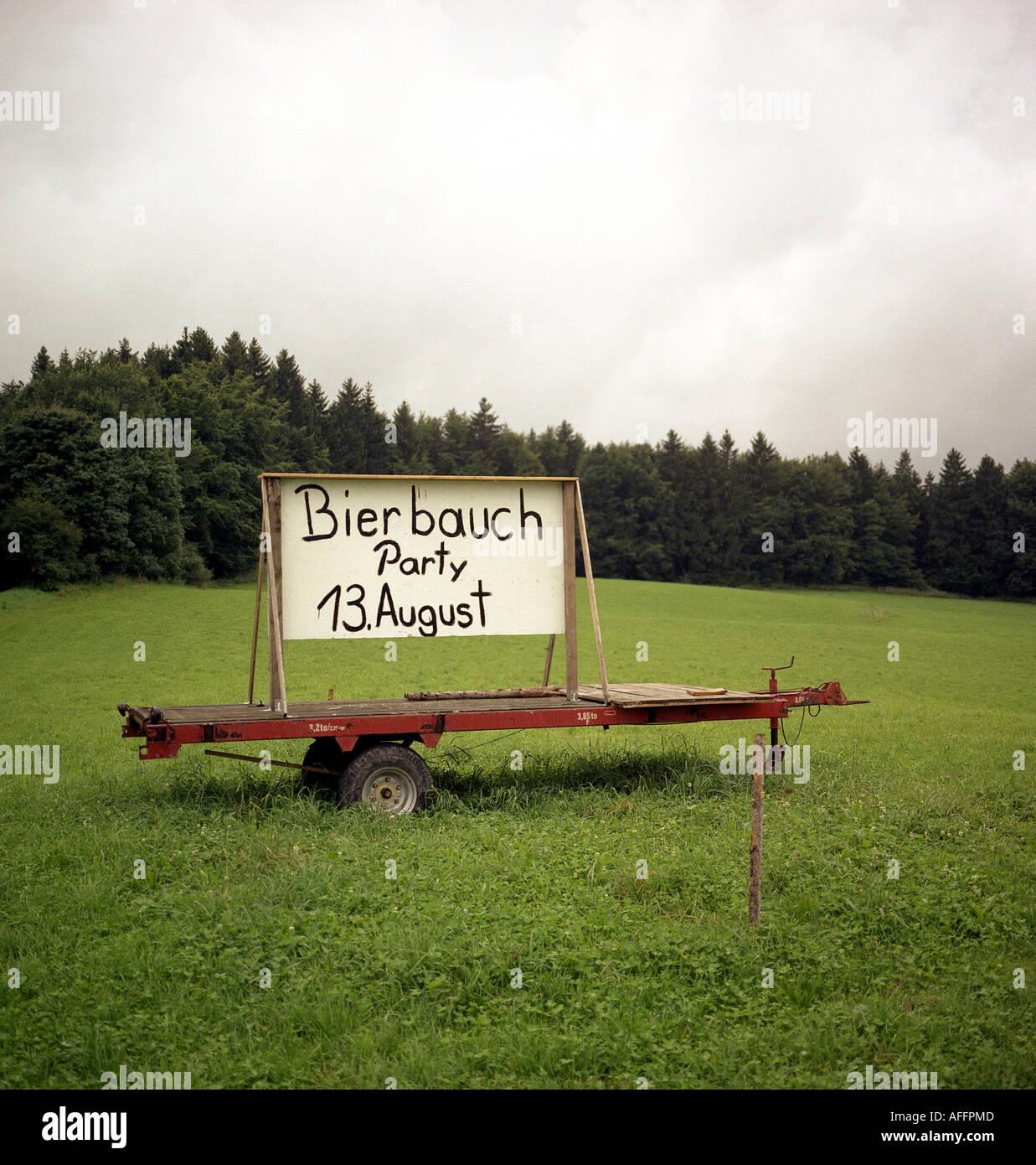 Plakat auf dem Haenger eines Traktors wirbt fuer eine Party in Bayern - Stock Image