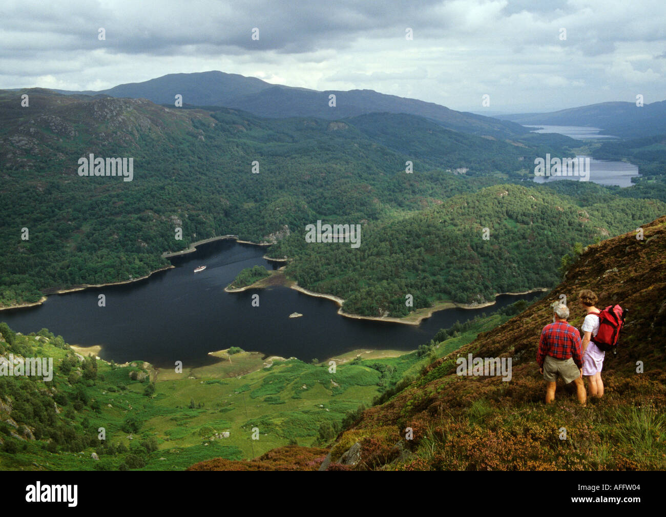 walkers on Ben Venue in the Trossachs with SS Sir Walter Scott on Loch Katrine - Stock Image