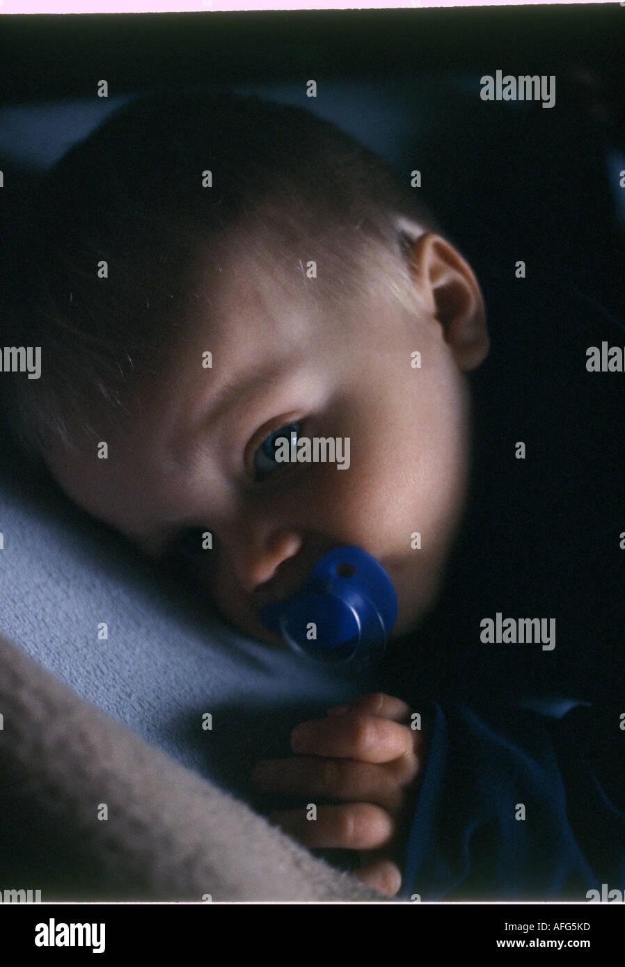 Baby mit Schnuller kurz vorm einschlafen - Stock Image