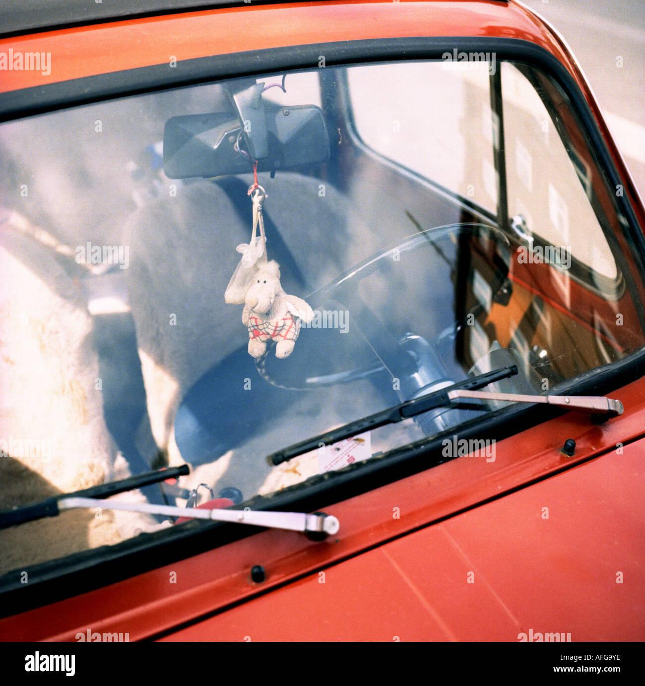 Windschutzscheibe an einem roten Fiat 500 mit Stoffpuppe am Innenspiegel - Stock Image