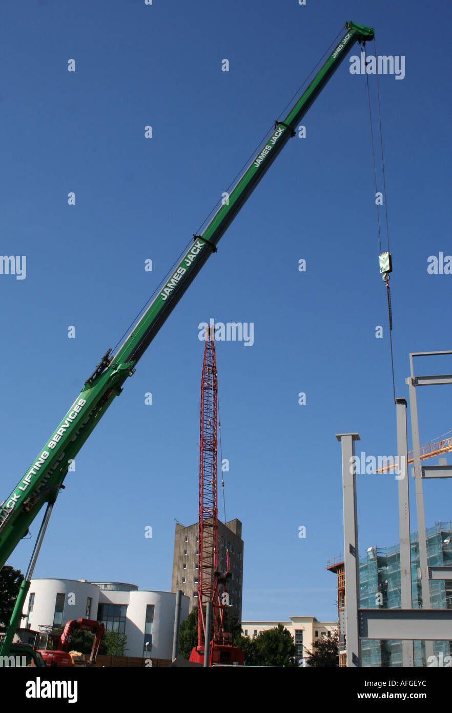 Green and red construction site crane Stock Photo