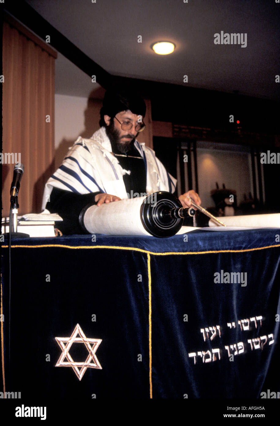 A rabbi reads from the scrolls in a Jewish reformed synagogue London - Stock Image