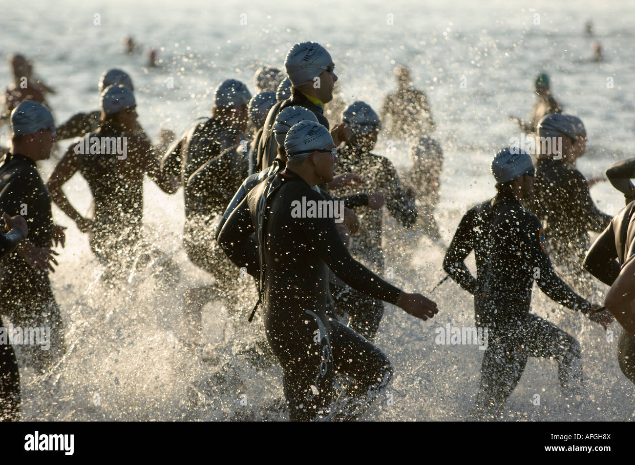Swimmers run into cold Pacific ocean for swimming section of
