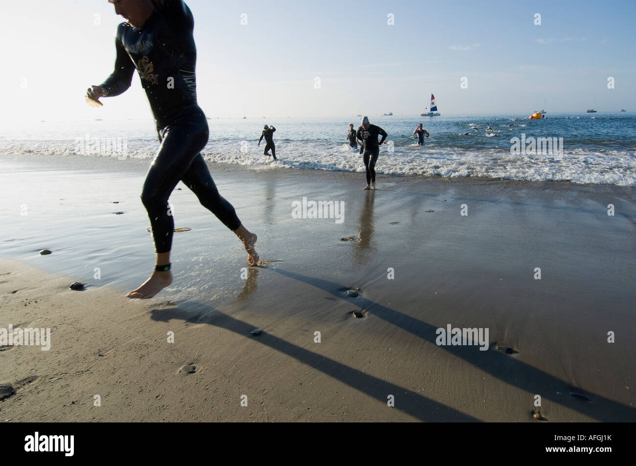 Racers exit water and run up beach after ocean swimming