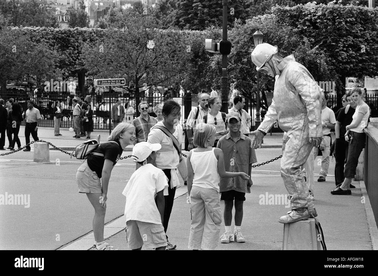 A street entertainer dreesed in silver entertains crowds in Paris France - Stock Image