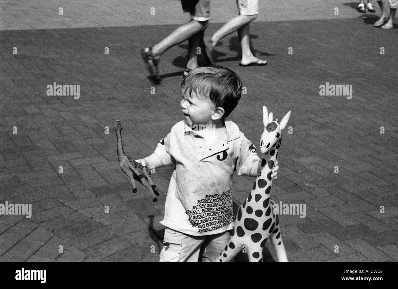 a young boy with toy giraffes - Stock Image