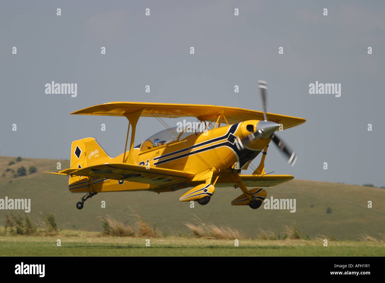 The Pitts S2 Special is a small acrobatic aerobatic precision flying competition airplane seen here landing on a grass runway - Stock Image