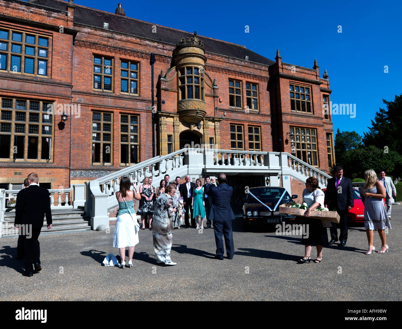 Guests at Wedding Reception and Cars at Woldingham Roman Catholic Boarding School Caterham Surrey England - Stock Image