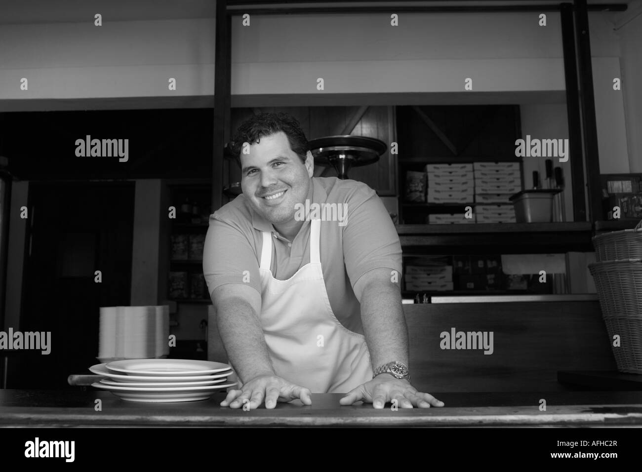Portrait of chef behind restaurant counter - Stock Image