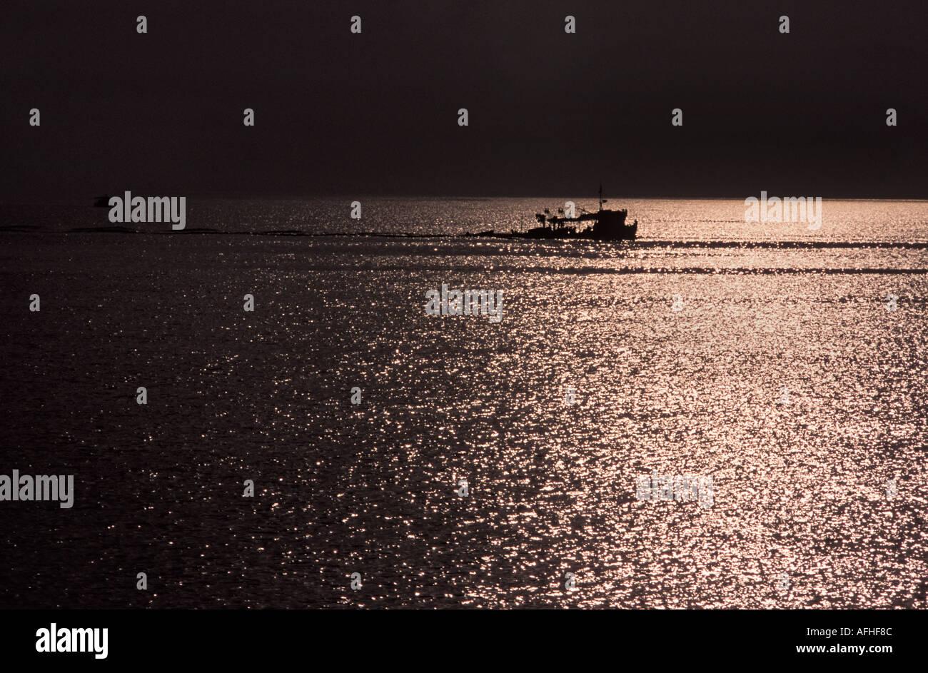 Boat silhouetted at sea off Zakynthos island En route to Kefallonia Zante Ionian Islands Greece Mediterranean Sea Europe - Stock Image