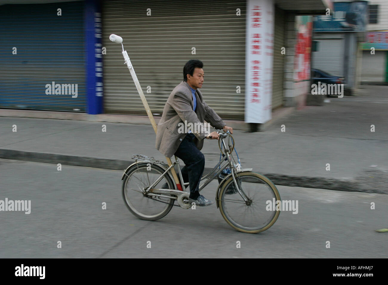 A decorator on his bicycle - Stock Image
