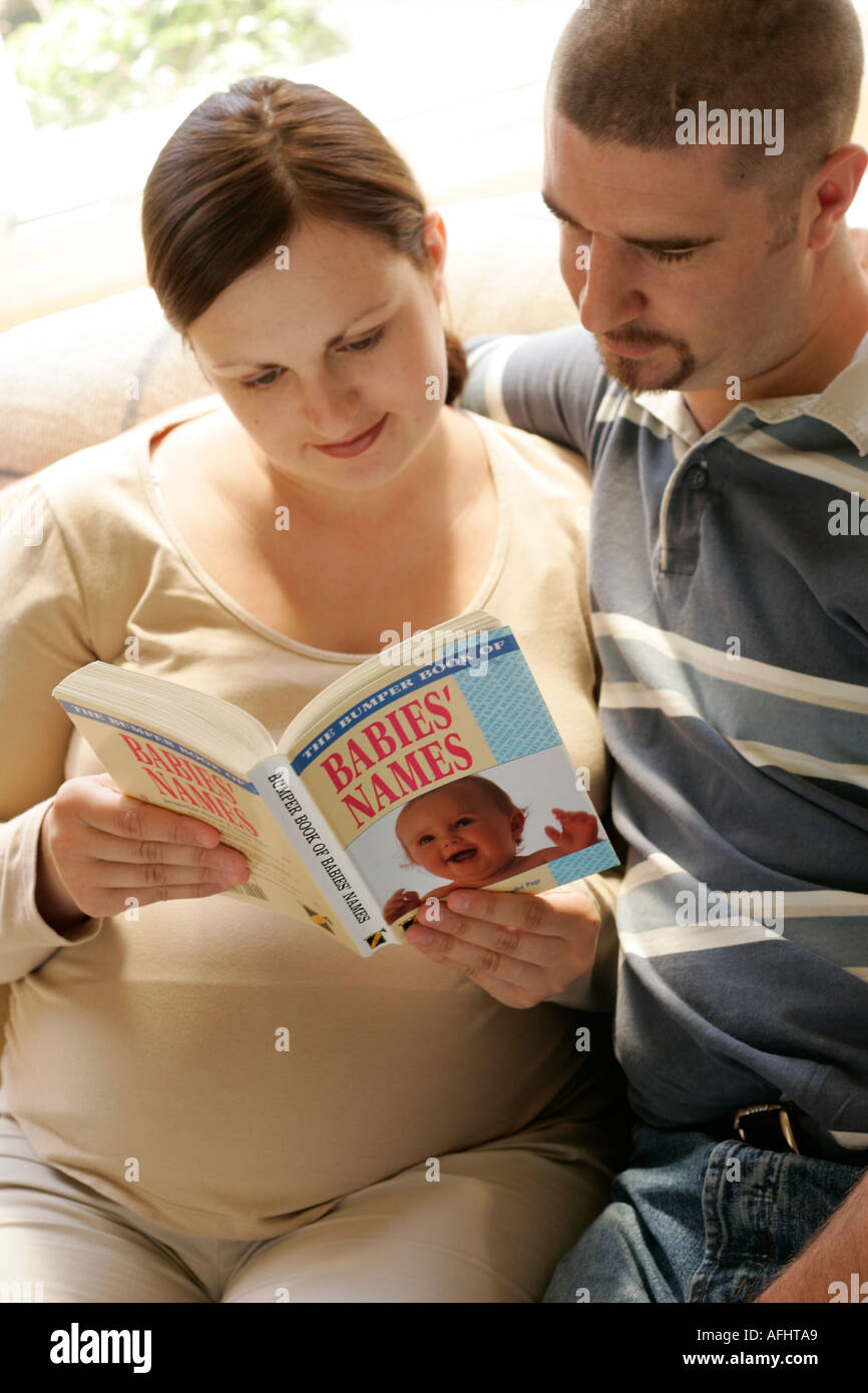 pregnant woman with her partner looking at a book of baby names - Stock Image