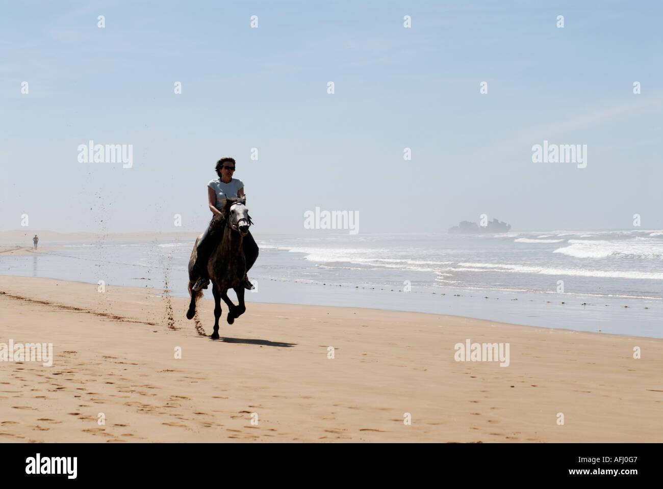 Female tourist riding horse on the beach Essaouira north Atlantic Morocco North Africa Kim Paumier - Stock Image