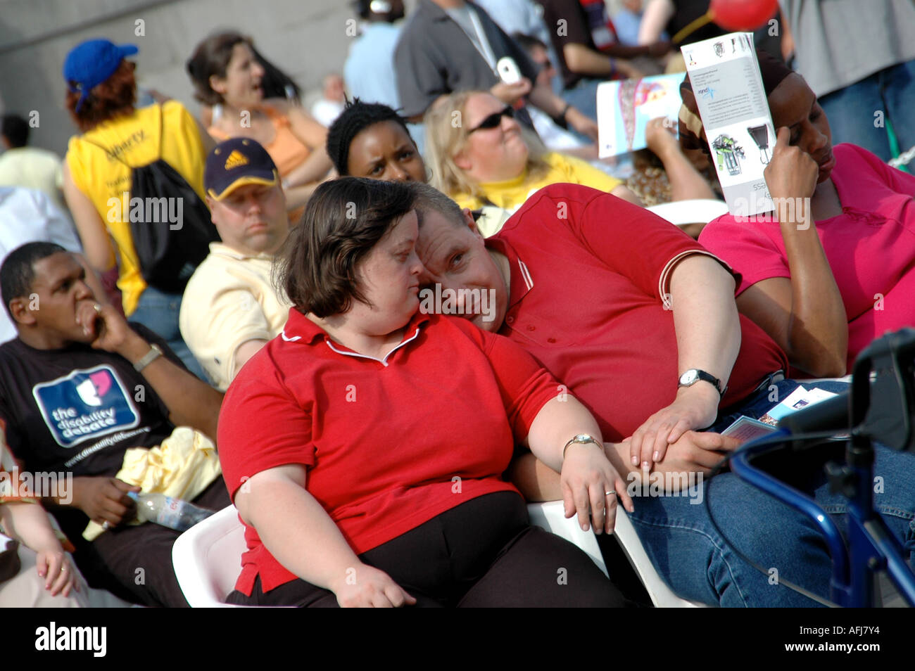 Disabled couple caught in a tender moment while watching the performances at the Liberty Festival, London - Stock Image