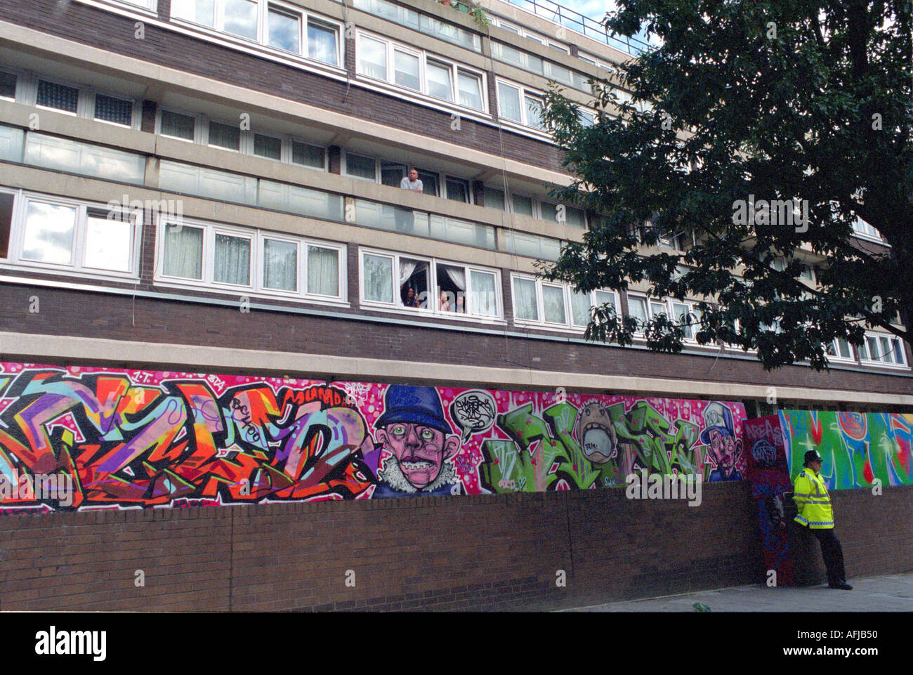 policeman on duty outside housing estate in west London with graffitti wall in background - Stock Image