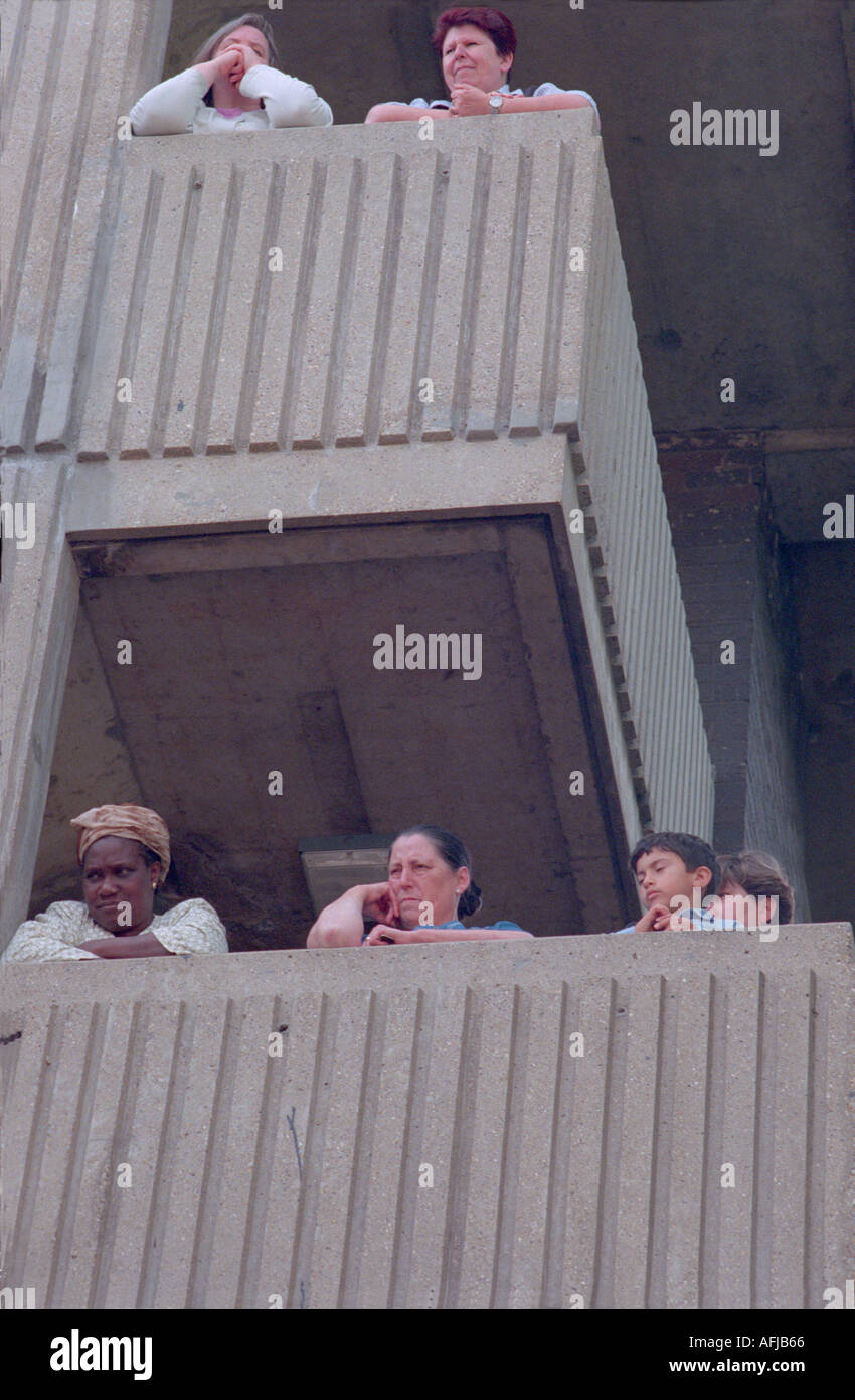Residents in West London housing estate on their balconies watching Notting hill carnival going by. Stock Photo