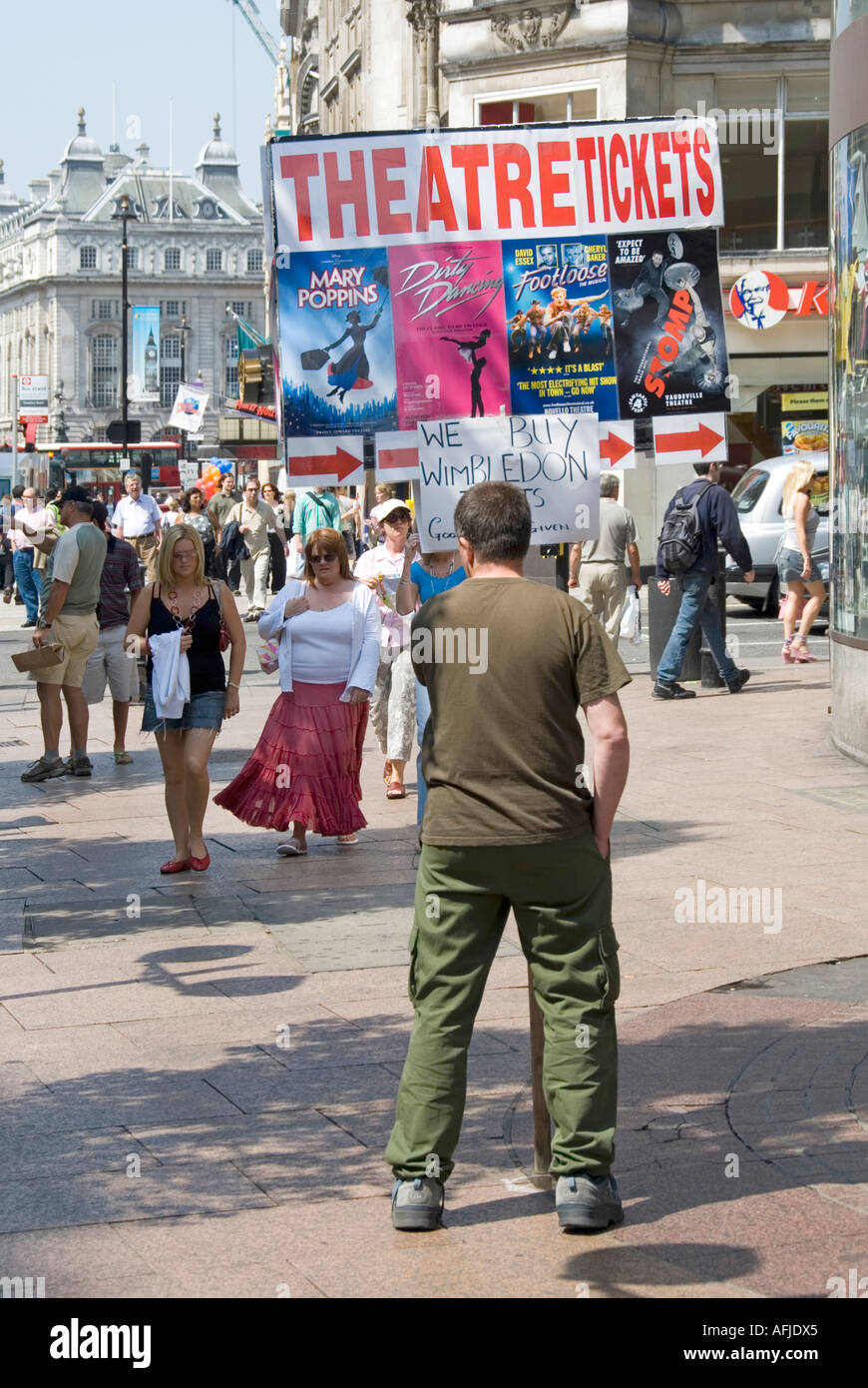 Leicester Square man holding advertising board pointing towards location for obtaining theatre and Wimbledon tennis tickets - Stock Image