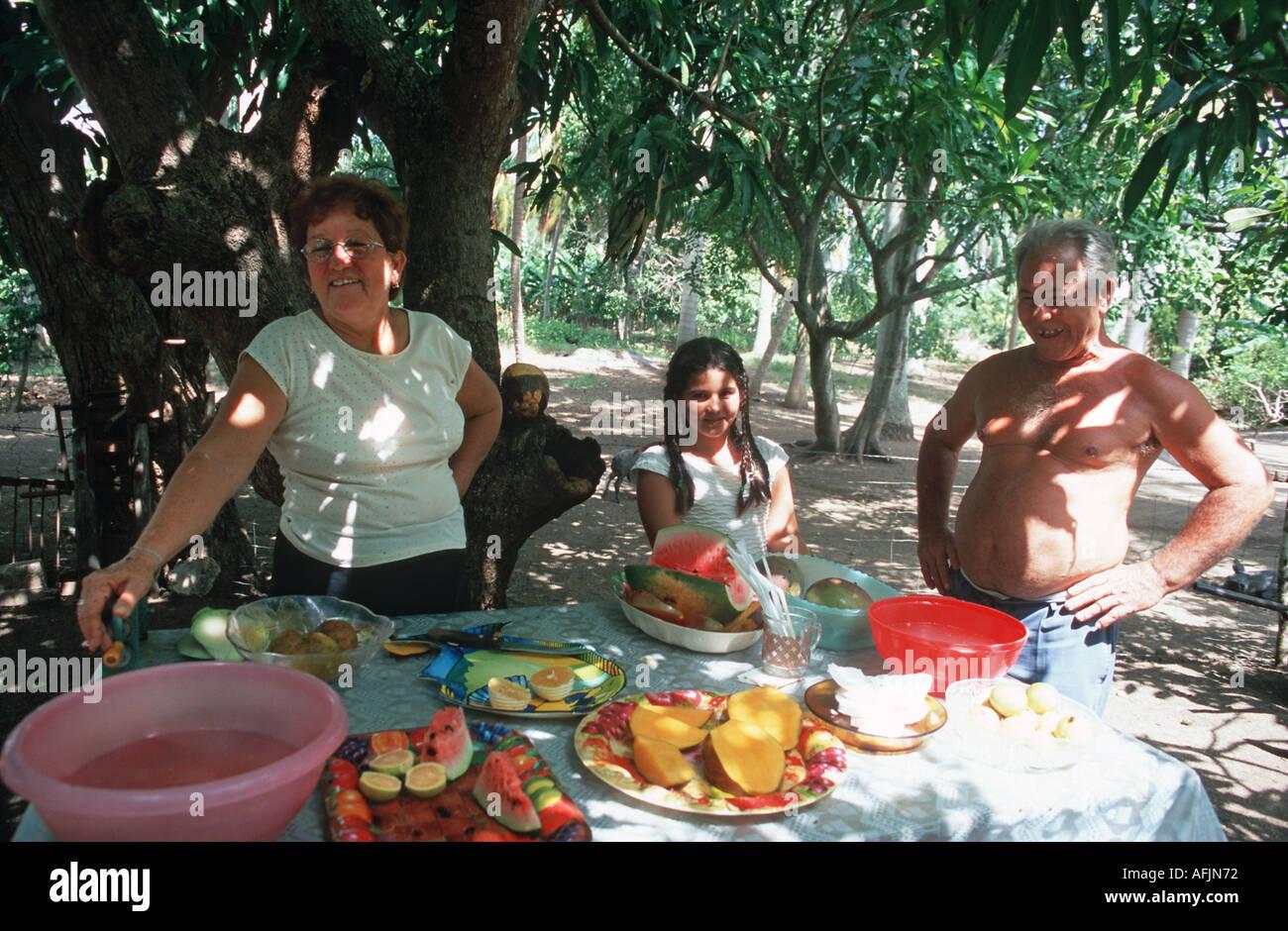 Farming family offering a spread of tropical fruits Holgiun Cuba - Stock Image