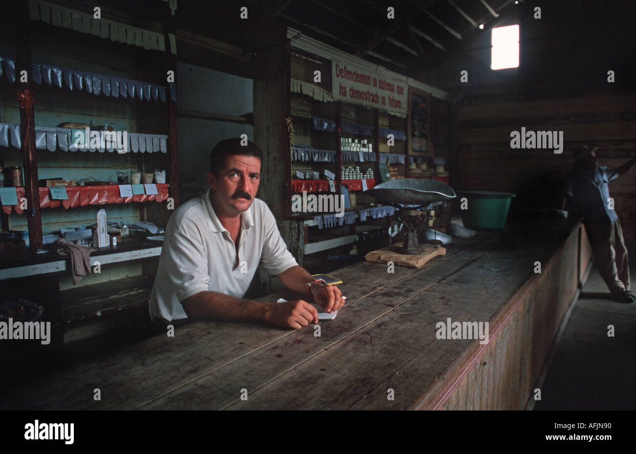 Shopkeeper at the government sponsored local store rationing products in short supply Holguin Cuba - Stock Image