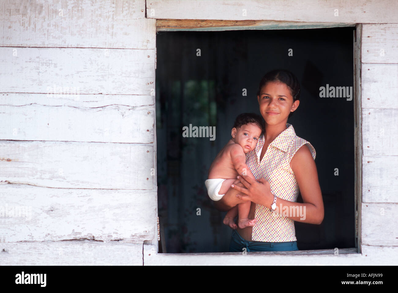 Young mother holding young baby in her arms and standing at the window to her home Holguin Cuba - Stock Image