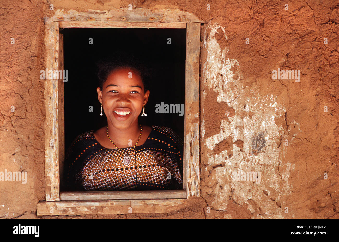 Local woman at the window to her adobe home Chole Island Mafia Island South of Zanzibar Tanzania East Africa - Stock Image