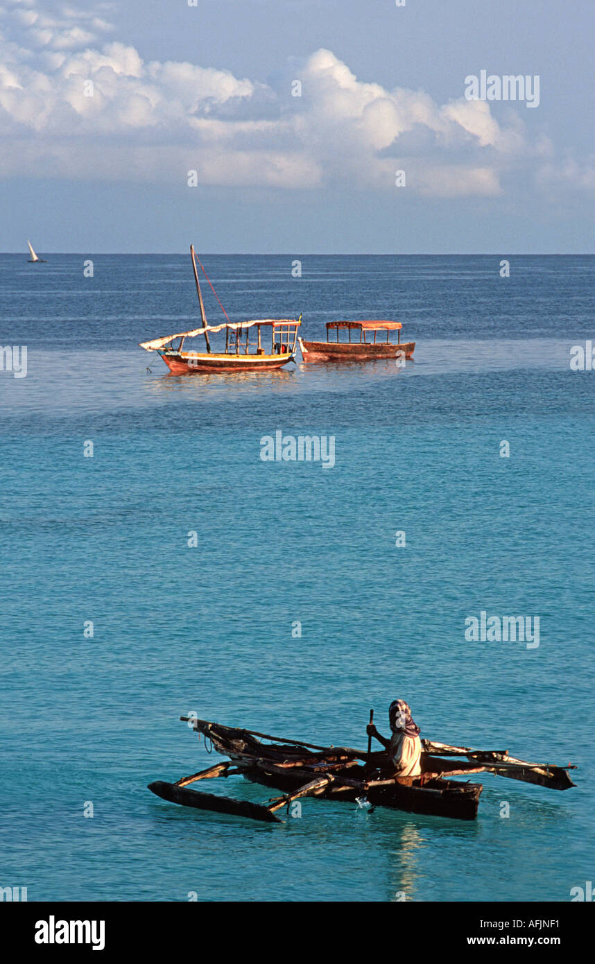 Fisherman sets out in his dug out outrigger canoe Nungwi Northern tip of Zanzibar Tanzania East Africa - Stock Image