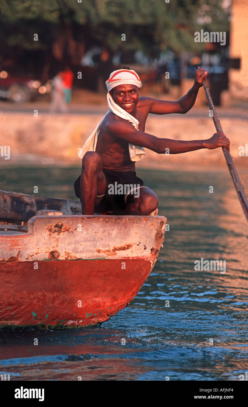 Fisherman with oar at sunset Stone Town waterfront Zanzibar Tanzania East Africa - Stock Image