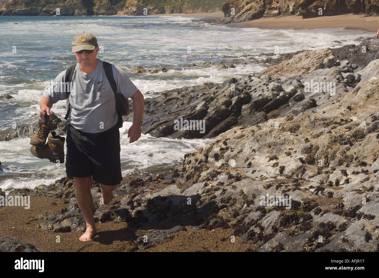 man in shorts a t shirt and baseball cap carrying hiking boots and wearing  a knapsack walking over barnacle covered rocks 98cda96c8f7