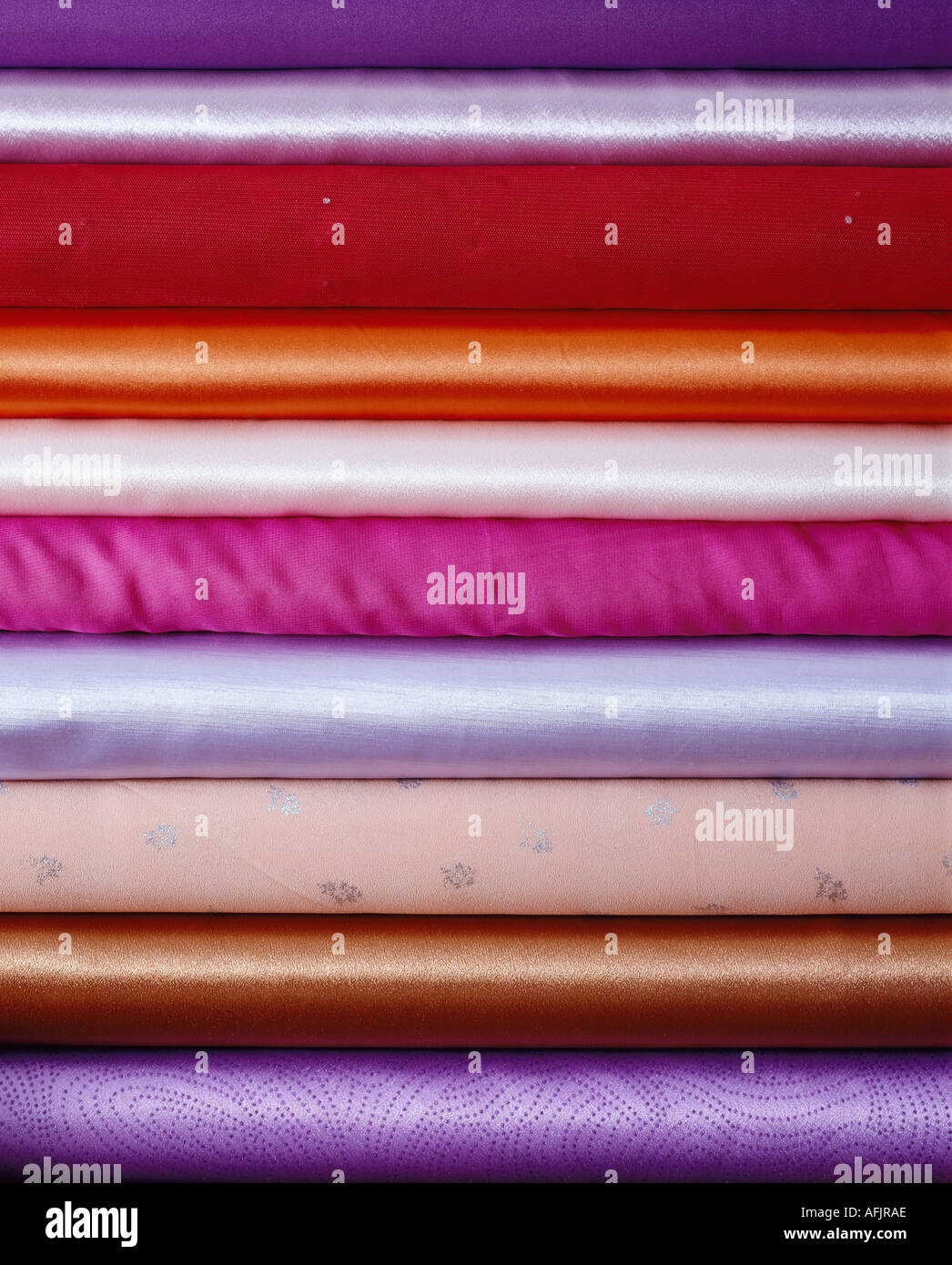 Graphic shot of pile of rolls of silk - Stock Image