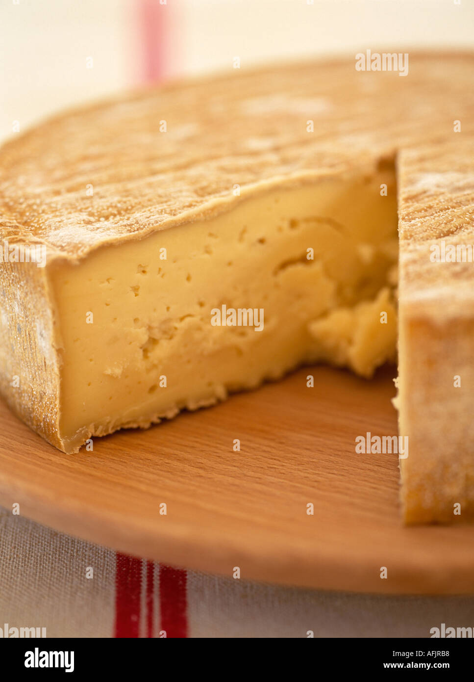 French cheese with wedge removed on wooden board and linen cloth - Stock Image