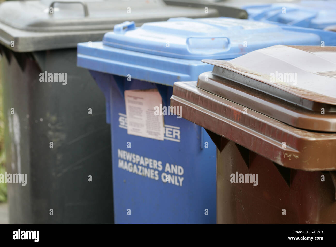A selection of waste bins including refuse paper recycling blue and garden waste recycling bin brown for a household Stock Photo