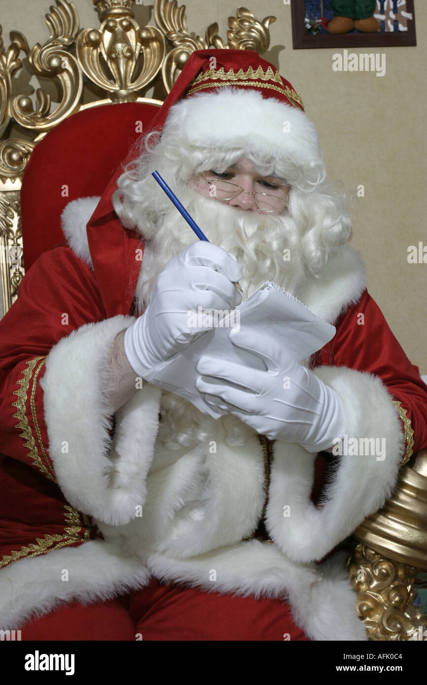 Santa Claus making a list on his throne - Stock Image