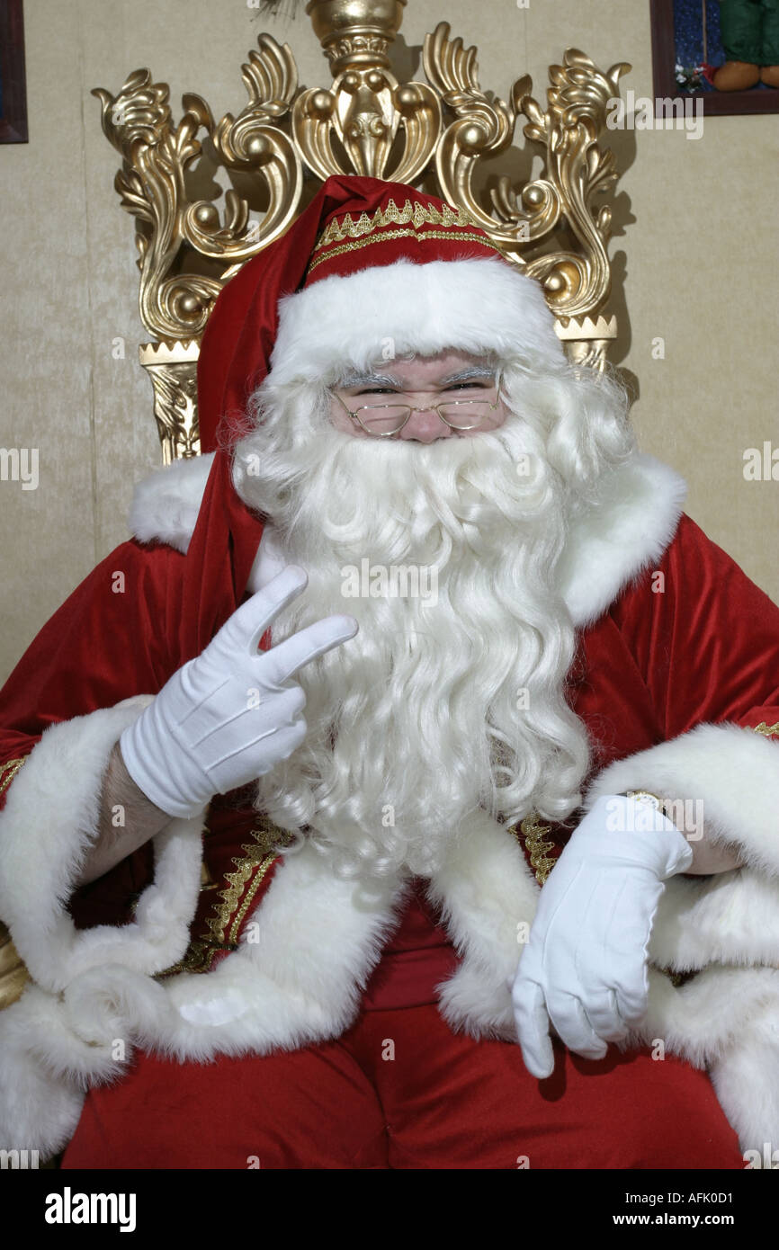 Nasty Santa Claus in his grotto with 2 two fingers up on his throne - Stock Image