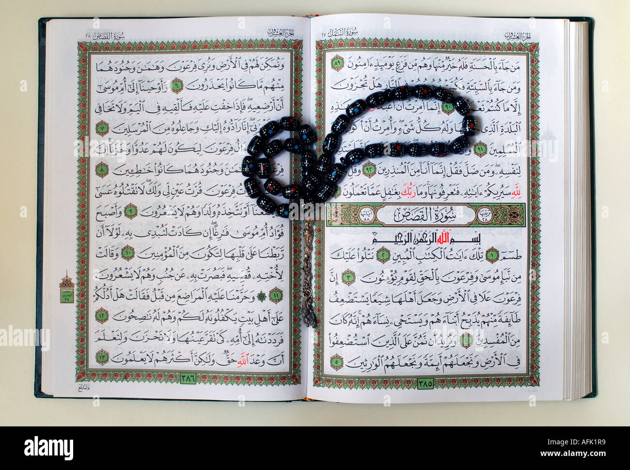 A copy of the sacred text of Islam Qur'an opened for reading with prayer beads called Tasbeeh - Stock Image