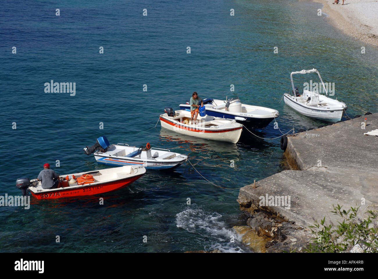 Five small boats with outboard motors moored to jetty and being prepared for hire - Stock Image