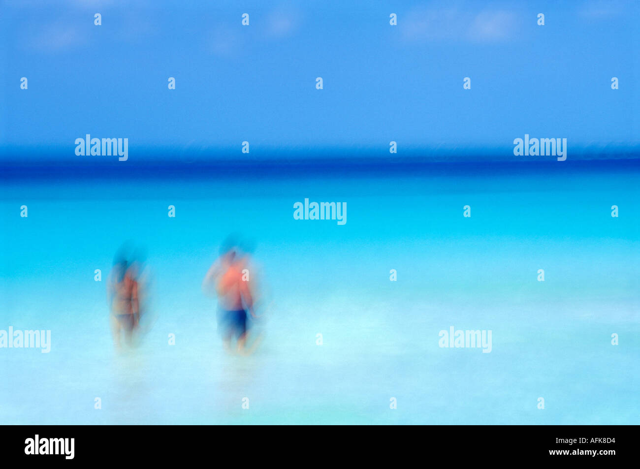 Blurred motion image of couple walking into the ocean in Cancun Mexico Model Released Image - Stock Image