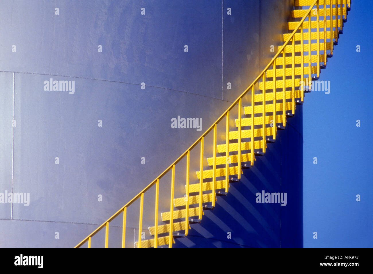 Yellow stairs on side of large petroleum storage tank - Stock Image