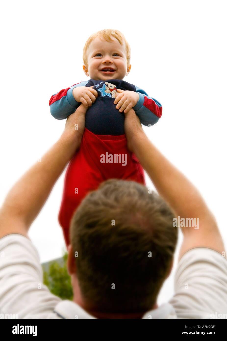 Happy baby boy held aloft by dad - Stock Image