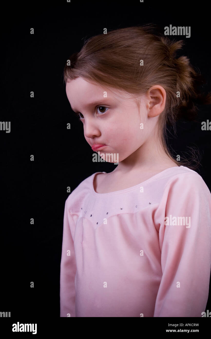 Little girl sticking out her lower lip in a defiant pout - Stock Image