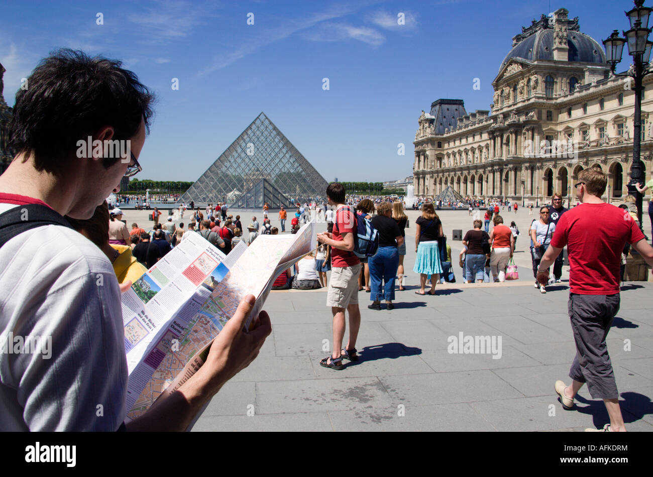 france ile de france paris tourist reading city map in square busy with people at louvre