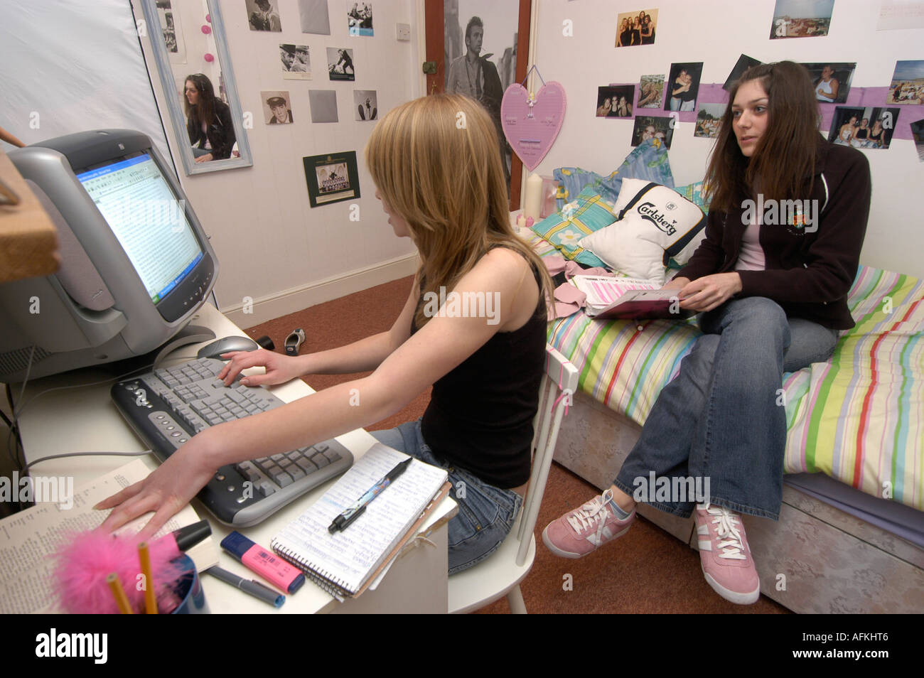 Women student working on her essay for college at home with help form her friend in her flat Aberystwyth Ceredigion Wales - Stock Image