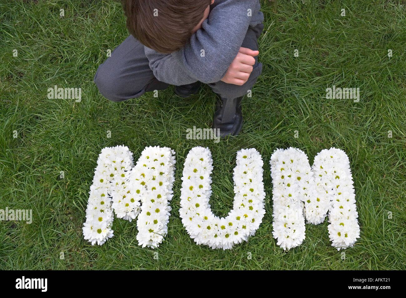 Funeral flowers mum stock photos funeral flowers mum stock images young boy kneeling down beside his mothers funeral flowers stock image izmirmasajfo